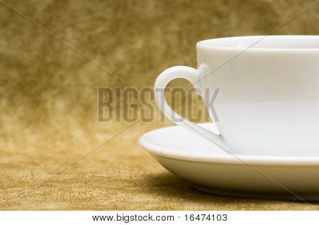 White cup with saucer over brown background