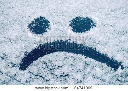 Sad smiley emoticon face drawn on snow covered glass winter season sadness concept