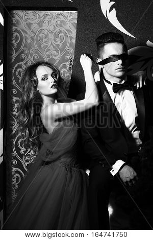 young couple of handsome man in suit and bow with pretty sexy woman in elegant evening dress with skirt and long curly hair black and white