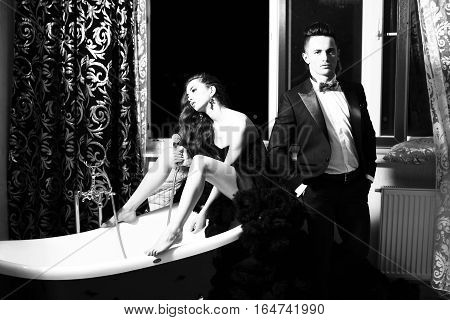 young handsome man in suit and bow with pretty sexy woman in elegant evening dress with skirt and long curly hair sitting in bath black and white