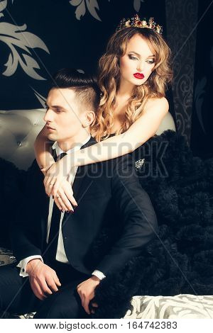 young couple of handsome man in black suit and bow with pretty sexy woman in elegant evening dress with skirt and long curly hair with crown and jewellery gem stone
