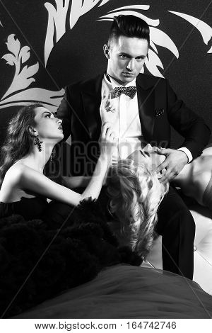 young handsome man in suit and bow with pretty sexy women in elegant evening dress with skirt and long curly hair on bed in bedroom black and white