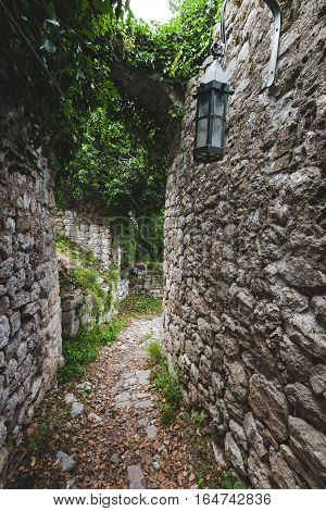 Ancient narrow street and ruined stone wall of Old Bar town, Montenegro. Stari Bar - ruined medieval city on Adriatic coast, Unesco World Heritage Site.