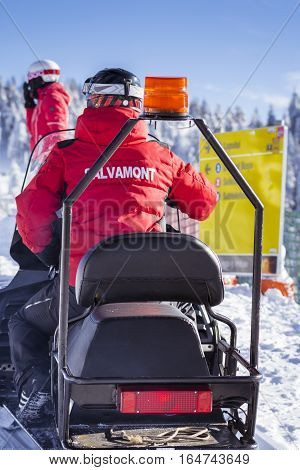 Poiana Brasov Romania- January 24 2016: Salvamont rescue team on ski slope. Man riding snowmobile using for rescue people in the winter season in Poiana Brasov Romania