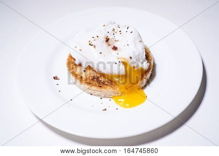 Poached egg on toasted toast on a white plate with spices