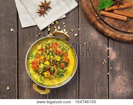 Vegan and vegetarian dish, spicy curry from tofu in copper bowl, top view. Indian cuisine with herbs, healthy meal on wooden served table background. Eastern local cuisine restaurant food.