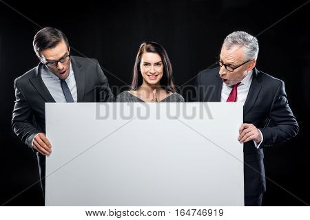 Three businespeople holding blank card on black