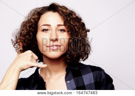 cute young attractive woman  holding hand near ear call, studio shot