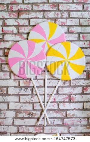 multi-colored lollypops at the brick wall background.