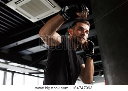 Male exercising in boxing black gloves in gym