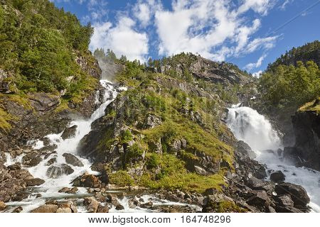 Norwegian twin waterfall. Rocky forest landscape. Latefossen. Visit Norway. Highlight