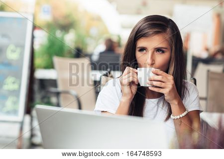 Attractive young brunette woman sitting at a sidewalk cafe using a laptop and drinking a cup of coffee