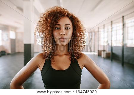 Portrait of beautiful afro american female with curly hair in gym. African fitness woman at healthclub.