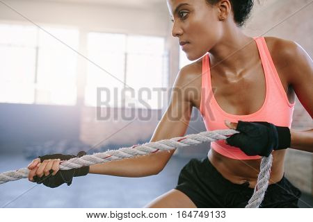 Close up shot of fit young woman exercising with rope at a gym. Strong african female pulling rope at gym.