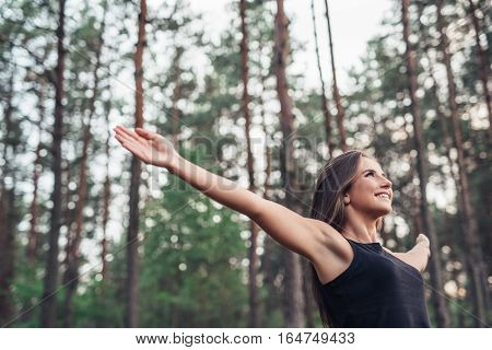 Attractive young brunette woman smilng while standing among trees in a forest with arms raised up to embrace nature