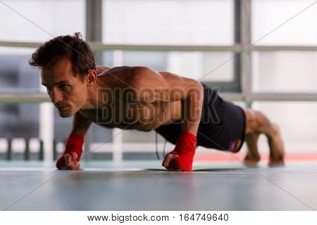 Man train in gym with boxing bandages