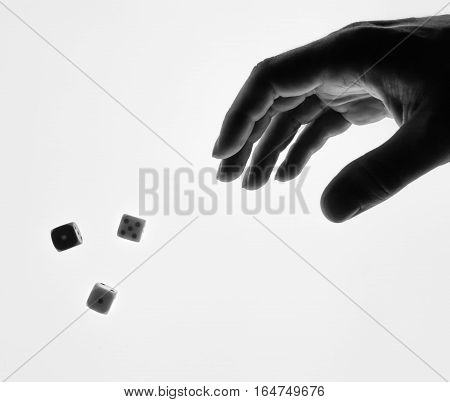 man's hand throwing dice on a white background