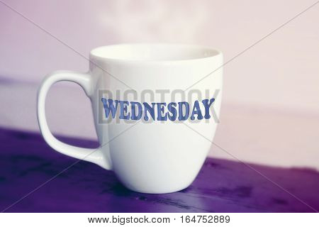 white cup with the word Wednesday on it on purple wooden table