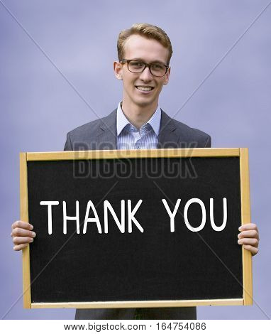 young businessman holding chalkboard with the words Thank You