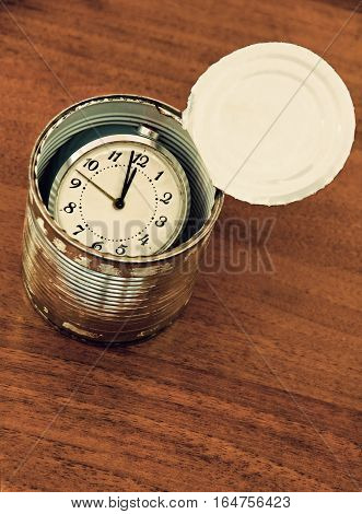 Canned time concept.Time preserved in tin can on wooden table taken closeup.