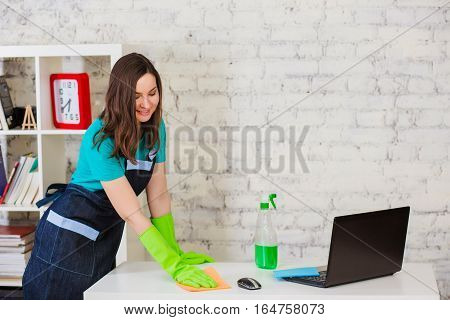 Positive female worker in uniform cleaning computer desk with spray and sponge at modern white office. Professional service cleaning