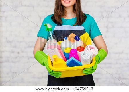 Female hands dressed green gloves holding bucket with many colorful detergent for cleaning house. On the soft-focus background a white brick wall