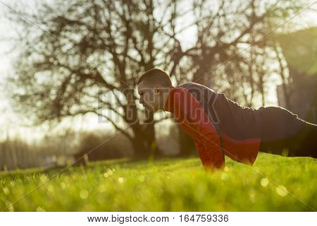 Young sportsman working out in a park, doing a series of push ups