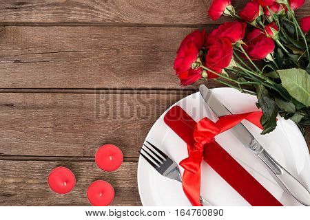 Valentines day table setting with plate, gift, red ribbon and roses. Valentines day background. Still life