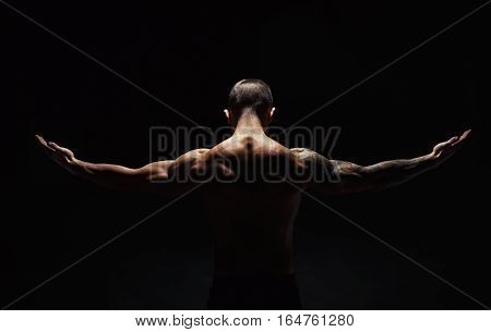 Unrecognizable man bodybuilder shows strong hands and neck muscles, athletic trapezius. Low key, studio shot on black background.