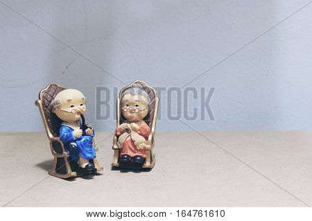 Still Life Photography With Lovely Grandpa Is Smoking And Grandma With Cat Doll Siting Rocking Bambo