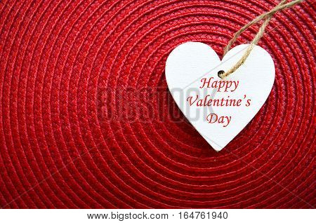 Happy Valentines Day background.Decorative white wooden heart on red straw napkin with copy space.Saint Valentine's Day concept. Selective focus. Saint Valentine's Day concept.