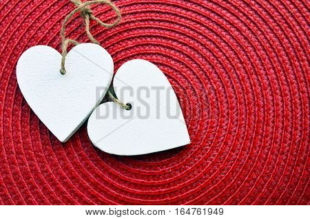 Decorative white wooden hearts on red straw napkin with copy space. Saint Valentine's Day or love concept.Two Valentine hearts.Valentine's Day background. Selective focus.