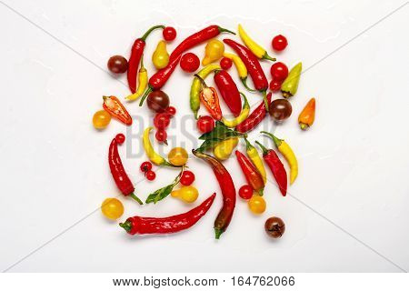 Plenty of green, yellow and red chili peppers and tomatoes isolated on white background. Closeup pile of ideal hot spicy and sweet vegetables, healthy natural organic food, top view