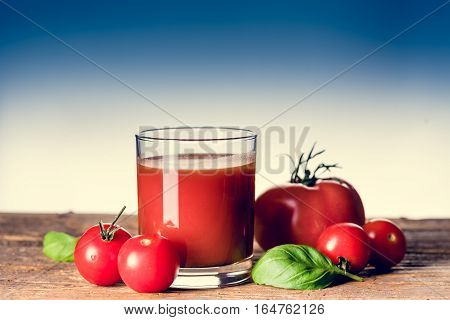 Tomato juice and a few small tomatos in the glass on the wooden table. Copy space
