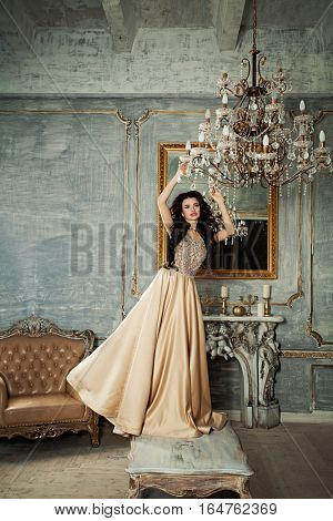 Beautiful Model Woman with Long Hairstyle Wearing Luxury Dress in Royal Interior