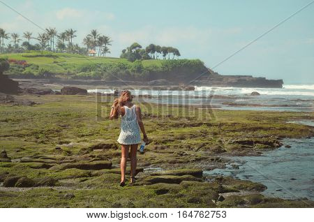 youngt woman on the beach exploring the cliffs of bali