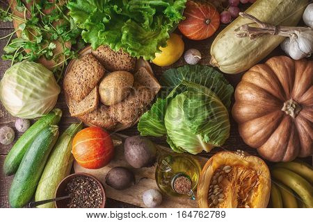 Grain bread with different vegetable on the wooden table top view. Concept of healthy food