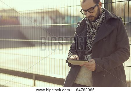 Young man surfing the internet on a tablet computer outdoor