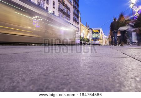 Streetcar that runs along downtown at night with Christmas decoration Seville Spain. Motion blurred