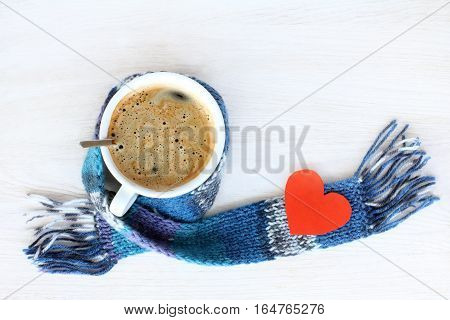 frothy coffee in a warming scarf and Valentine card top view / drink for favorite person