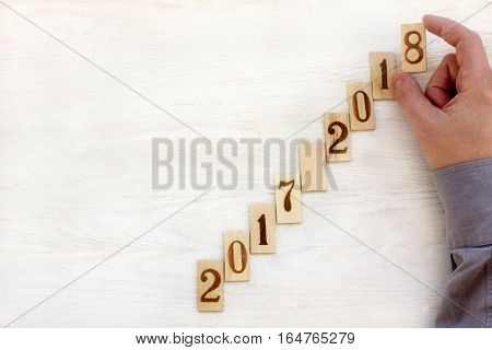 Hand puts the ladder of plates with numbers top view / moving up every year
