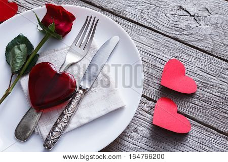 Romantic dinner concept. Valentine day or proposal background. Top view of restaurant wooden table with glass heart and rose with cutlery on plate on rustic wood