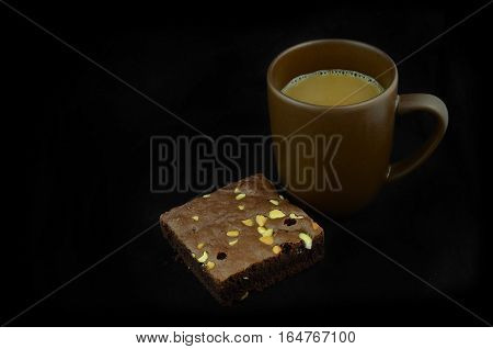 Closeup of coffee cup and brownies on a black background.
