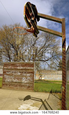 A basketball backboard, hoop, and net in an outdoor court finds a wall with scribbling and words.