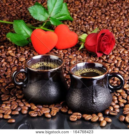 Two cups of black coffee with foam on the background from the fried coffee beans, small hearts and a red rose. For cards for Valentine's Day.