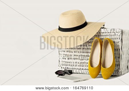 White wicker suitcase women's hat sunglasses yellow shoes and e-book.