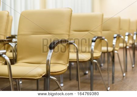 Rows of metal chairs at the conference in an empty room. Front view.