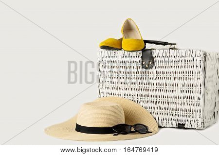 White wicker suitcase women's hat sunglasses and yellow shoes.