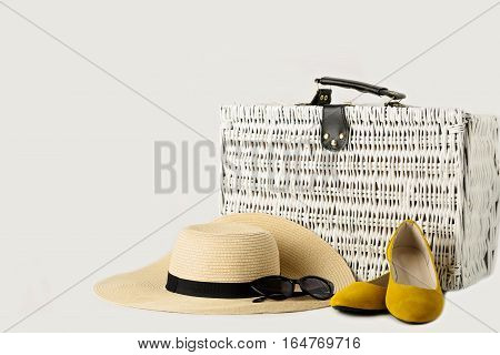 White wicker suitcase womens hat sunglasses and yellow shoes.