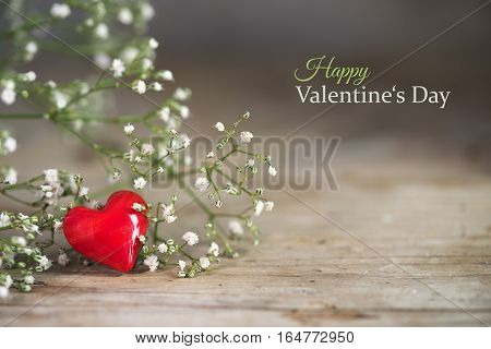 Small red heart from glass and white flowers on a rustic wooden background love concept sample text Happy Valentine's Day